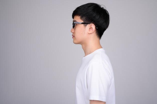 Młody mężczyzna azjatyckich noszenie okularów na białym tle
