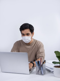 Młody mężczyzna azjatyckich ubrany w maskę ochronną, pracujący projekt na swoim komputerze przenośnym w biurze. studio strzał na białym tle.