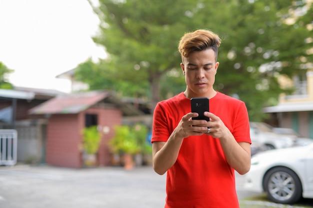 Młody mężczyzna azjatyckich za pomocą telefonu na ulicach na zewnątrz