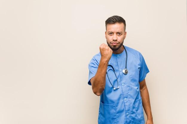Młody mężczyzna azji południowo-wschodniej pielęgniarki pokazując pięść do aparatu, agresywny wyraz twarzy.