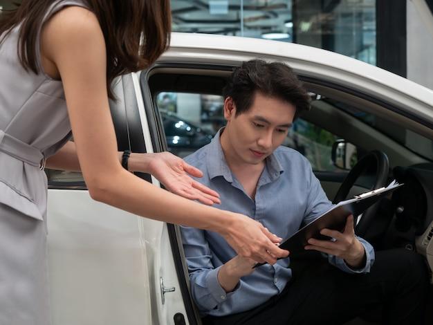 Młody mężczyzna azji rozmawia z kierownikiem sprzedaży, wybierając samochód w salonie.