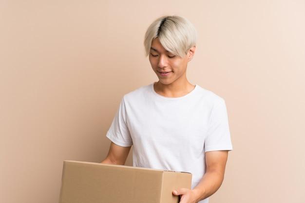 Młody mężczyzna azji, trzymając pudełko, aby przenieść go do innej witryny