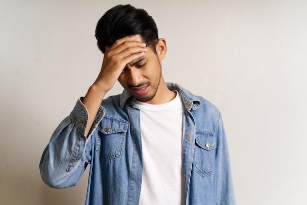 Młody mężczyzna azji umieścić rękę na głowie. ma mdłości i ból głowy.