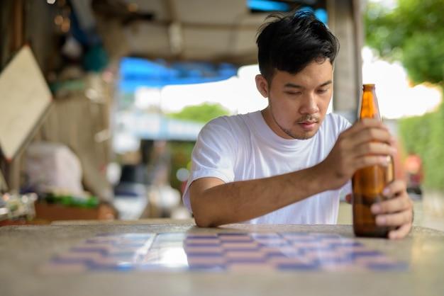 Młody mężczyzna azji upija się na ulicach na zewnątrz
