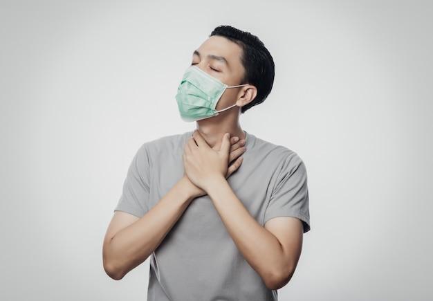 Młody mężczyzna azji w higienicznej masce cierpi na ból gardła, koronawirusa. choroby układu oddechowego przenoszone drogą powietrzną, takie jak walka po południu i grypa. studio strzelający odizolowywającym na białym tle.