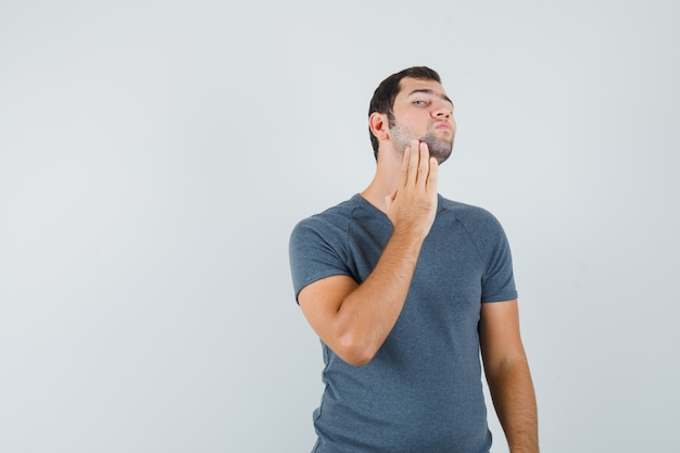 Młody mężczyzna bada skórę twarzy, dotykając brody w szarym t-shircie i wyglądając przystojnie