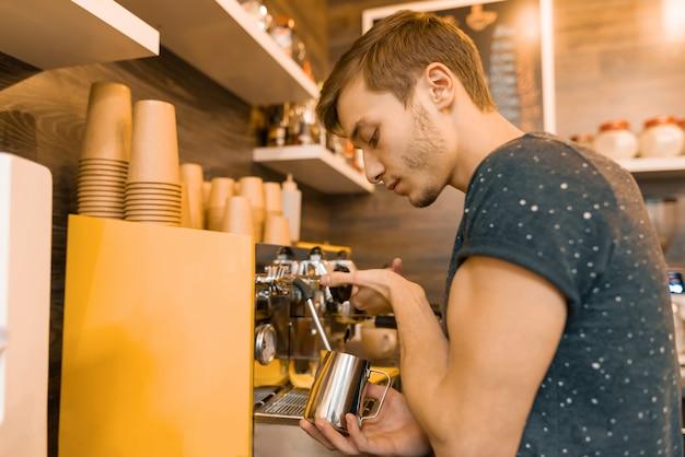 Młody mężczyzna barista sprawia, że napój