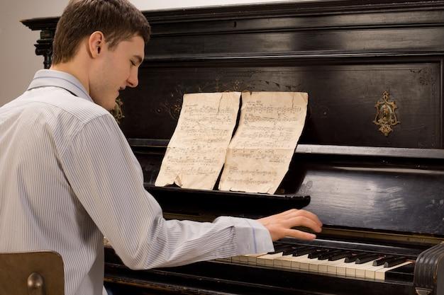 Młody mężczyzna bawi się grając na pianinie