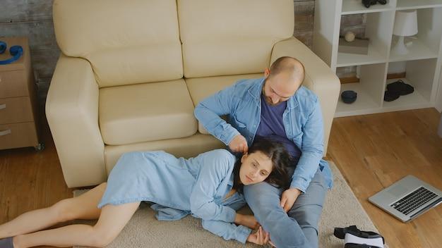 Młody mężczyzna bawi się włosami żony, relaksując się na dywanie.
