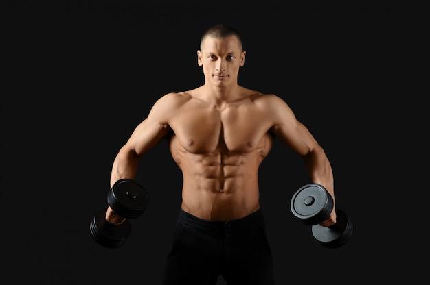 Młody mężczyzna bez koszuli pompujący żelazko, pokazujący swoje zgrane mięśnie brzucha