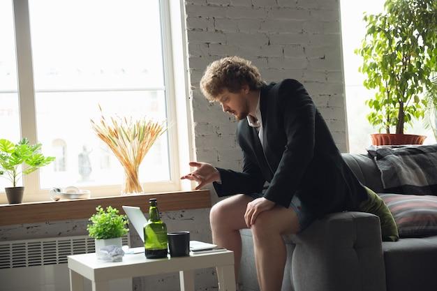 Młody mężczyzna bez spodni, ale w kurtce, pracujący na komputerze laptop w zdalnym biurze podczas koronawirusa
