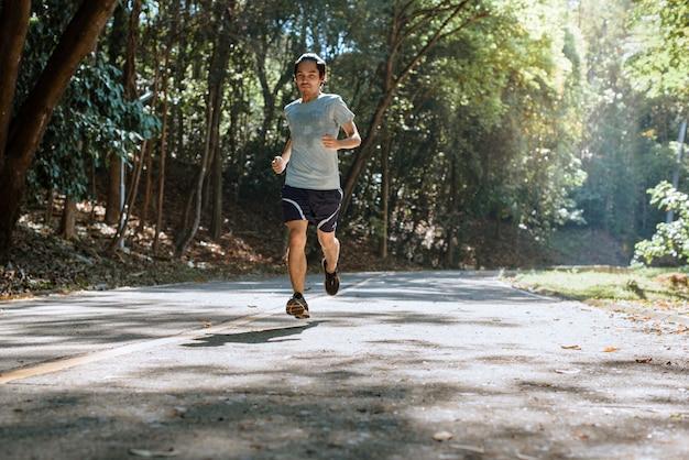 Młody mężczyzna biegacz sportowiec działa na jeździe