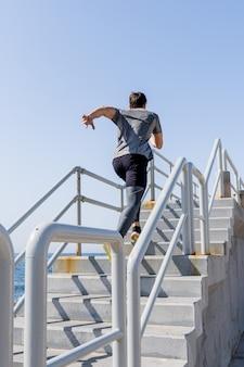 Młody mężczyzna biegający po schodach na zewnątrz z czystym niebem w porcie, za widokiem
