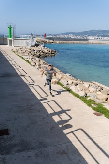 Młody mężczyzna biegnący przez port podczas treningu w południe