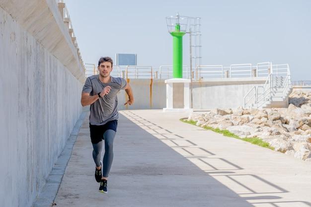Młody mężczyzna biegnący wzdłuż promenady w pobliżu latarni morskiej w porcie