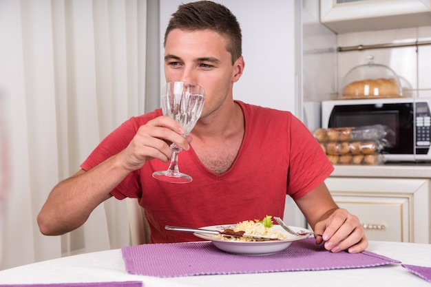 Młody mężczyzna bierze łyk wody podczas kolacji domowej roboty makaronu siedząc przy stole w uroczej kuchni