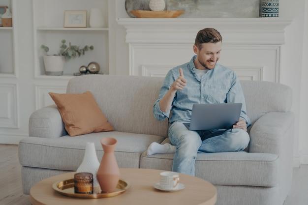 Młody mężczyzna biznesmen siedzący na kanapie ze skrzyżowaną nogą, pokazujący kciuk w górę gest swoim współpracownikom podczas spotkania online, wyrażający swoje zadowolenie z wykonanej pracy