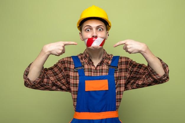 Młody mężczyzna budowniczy noszący jednolite, zapieczętowane usta z taśmą klejącą odizolowaną na oliwkowozielonej ścianie