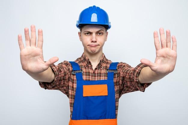 Młody mężczyzna budowniczy ubrany w mundur na białej ścianie