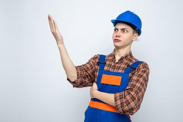 Młody mężczyzna budowniczy ubrany w mundur na białym tle na białej ścianie z miejscem na kopię