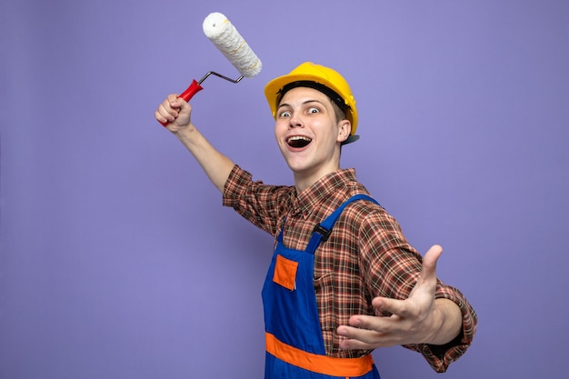 Młody mężczyzna budowniczy ubrany w mundur trzymający szczotkę rolkową na fioletowej ścianie