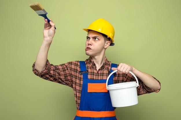 Młody mężczyzna budowniczy ubrany w mundur, trzymający wiadro z pędzlem na białym tle na oliwkowozielonej ścianie