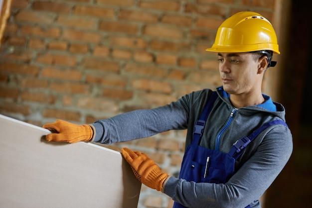 Młody mężczyzna budowniczy w kasku używającym, trzymający płytę gipsowo-kartonową podczas pracy na budowie