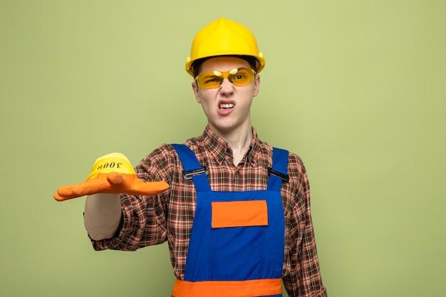 Młody mężczyzna budowniczy w mundurze i rękawiczkach w okularach odizolowanych na oliwkowozielonej ścianie