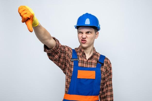 Młody mężczyzna budowniczy w mundurze z rękawiczkami na białym tle na białej ścianie