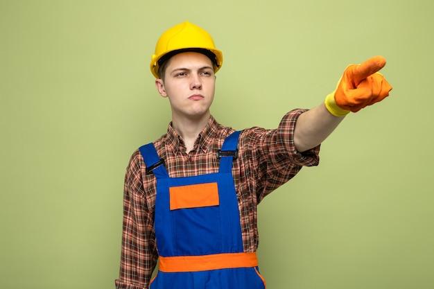 Młody mężczyzna budowniczy w mundurze z rękawiczkami odizolowanymi na oliwkowozielonej ścianie