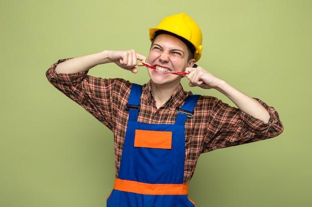 Młody mężczyzna budowniczy zapieczętował usta taśmą klejącą w mundurze odizolowanym na oliwkowozielonej ścianie