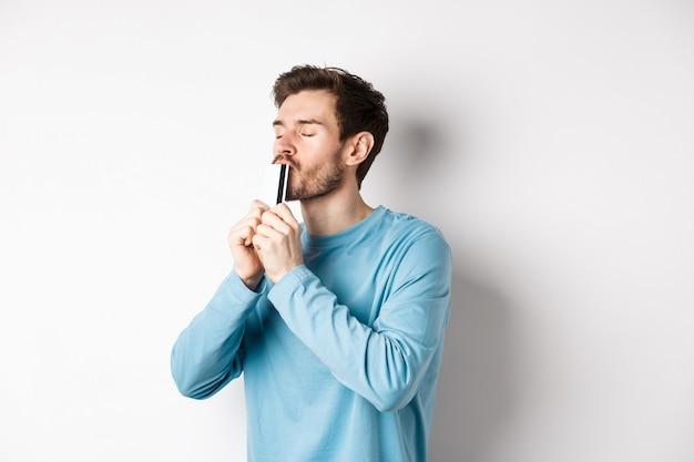 Młody mężczyzna całuje plastikową kartę kredytową z zadowoloną twarzą, stojąc na białym tle w niebieskiej koszuli na co dzień.