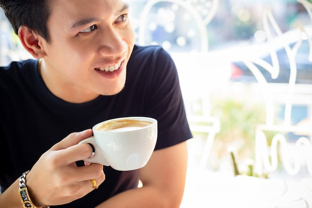 Młody mężczyzna chętnie pije kawę