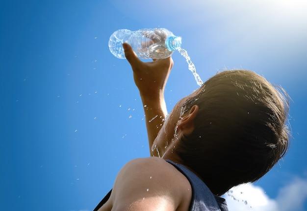 Młody mężczyzna chlapiący i nalewający świeżą wodę z butelki na twarzy, aby odświeżyć się w gorącym słońcu