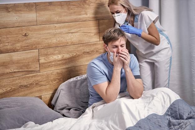 Młody mężczyzna chory na wirusową infekcję grypy w kwarantannie izolacji domowej, leży na łóżku, podczas gdy lekarz słucha oddechu za pomocą stetoskopu. koncepcja covid-19
