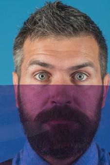 Młody mężczyzna chowa twarz za kolorowym szkłem i patrzy na kamerę odizolowaną na niebieskim tle
