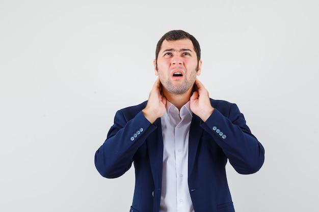 Młody mężczyzna cierpi na ból szyi w koszuli, kurtce i wygląda na zmęczonego