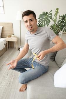 Młody mężczyzna cierpiący na anoreksję z miarką w sypialni