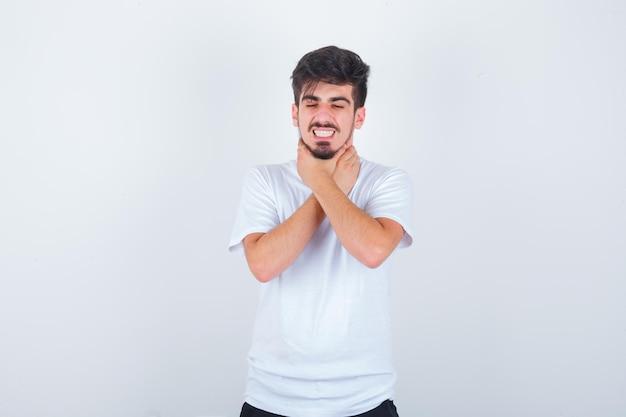 Młody mężczyzna cierpiący na ból gardła w białej koszulce i wyglądający na chorego