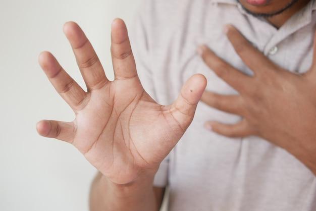 Młody mężczyzna cierpiący na ból w sercu i trzymający za rękę klatkę piersiową