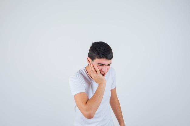 Młody mężczyzna cierpiący na ból zęba w koszulce i bolesny, widok z przodu.