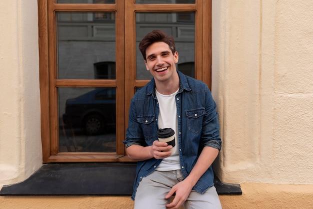 Młody mężczyzna cieszący się filiżanką kawy