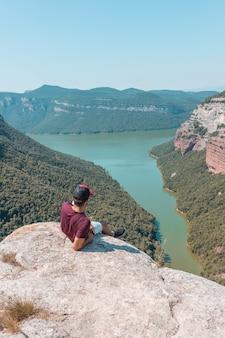 Młody mężczyzna cieszący się hipnotyzującą scenerią morro de la abeja w tavertet, katalonia, hiszpania