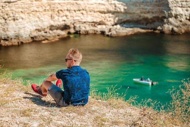 Młody mężczyzna cieszy się malowniczym pejzażem morskim z lazurową wodą na zachodnim wybrzeżu krymu