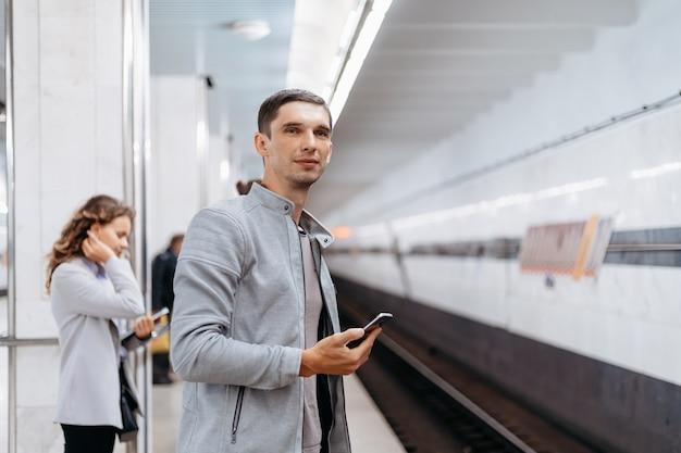 Młody mężczyzna czeka na pociąg na peronie metra