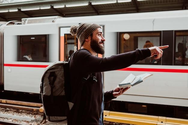 Młody mężczyzna czeka na stacji kolejowej