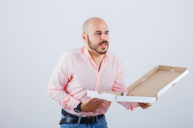 Młody mężczyzna czuje mdłości w koszuli, dżinsach i źle wygląda. przedni widok.