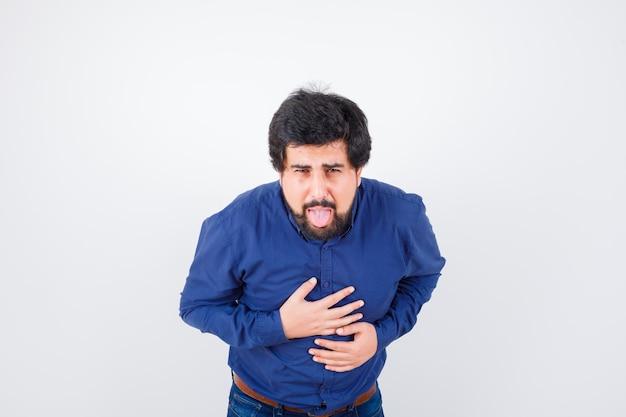 Młody mężczyzna czuje mdłości w niebieskiej koszuli i wygląda źle. przedni widok.