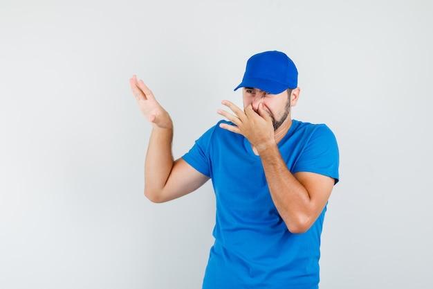 Młody mężczyzna czuje nieprzyjemny zapach w niebieskiej koszulce i czapce i wygląda na zniesmaczonego