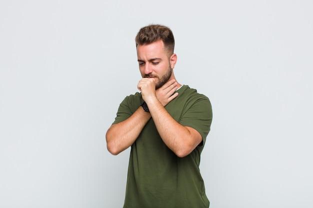 Młody mężczyzna czuje się chory z bólem gardła i objawami grypy, kaszle z zakrytymi ustami